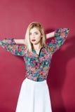 Портрет изумляя блондинкы в красочных рубашке и юбке белизны смотрит камеру на розовой предпосылке девушка чувственная Стоковое Изображение