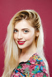 Портрет изумляя блондинкы при длинные волосы смотря камеру и усмехаясь на розовой предпосылке в студии Стоковые Изображения RF