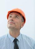 Портрет инженера в оранжевом шлеме смотря вверх Стоковая Фотография