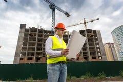 Портрет инженера по строительству и монтажу смотря светокопии на строительной площадке Стоковое Фото