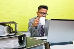 Портрет индийского бизнесмена держа кружку и работая на его портативном компьютере на его столе Стоковое Изображение RF