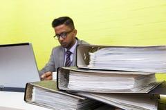 Портрет индийского бизнесмена работая на его портативном компьютере на его столе Стоковое Фото