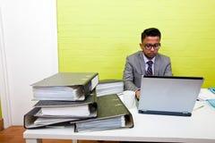 Портрет индийского бизнесмена работая на его портативном компьютере на его столе Стоковая Фотография