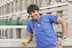 Портрет индийского мужского доктора держа зеленое яблоко Стоковое фото RF