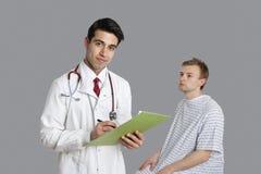 Портрет индийского сочинительства доктора на доске сзажимом для бумаги с усаживанием пациента кроме того Стоковое Изображение RF