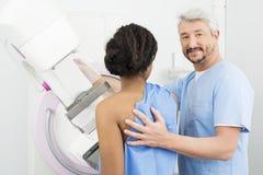 Портрет испытания доктора Assisting Пациента Undergoing Маммограммы Стоковые Изображения RF