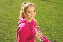 Портрет испытывающей жажду молодой красивой питьевой воды девушки фитнеса белокурых волос на стадионе Деятельность при спорта лет Стоковое Изображение