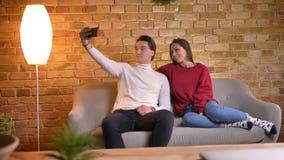 Портрет кавказских друзей делая selfie-фото используя смартфон и выбирая самые лучшие одни в домашней атмосфере видеоматериал