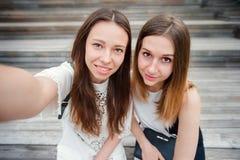 Портрет кавказских красивых девушек делая selfie outdoors Молодые туристские друзья путешествуя на усмехаться праздников счастлив Стоковое фото RF