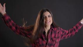 Портрет кавказской длинн-с волосами девушки брюнета закручивая для того чтобы показать счастье на черной предпосылке видеоматериал