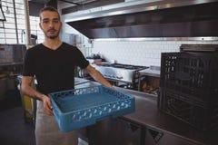 Портрет кельнера держа голубую клеть в кухне Стоковая Фотография