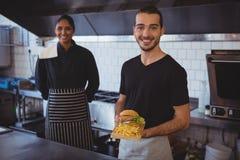 Портрет кельнера при сотрудник держа поднос еды в кафе Стоковые Фотографии RF