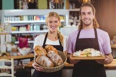Портрет кельнера и официантки держа поднос хлеба и еды Стоковые Фото