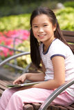 Портрет китайской девушки сидя на стенде парка Стоковые Изображения