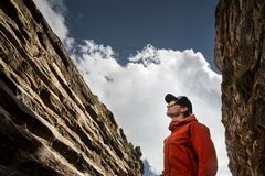 Портрет клипера в куртке мембраны с крышкой и солнечными очками в узком ущелье структурного утеса против стоковая фотография