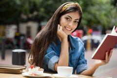 Портрет книги чтения женщины пока сидящ на стуле на кафе Стоковое Фото