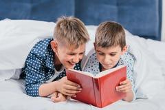 портрет книги чтения мальчиков пока лежащ под одеялом Стоковое Изображение RF