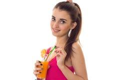 Портрет коктеиля и усмехаться жизнерадостных молодых пить женщины брюнет оранжевого на камере изолированной на белой предпосылке Стоковая Фотография