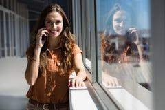Портрет коммерсантки говоря на мобильном телефоне окном на офисе Стоковая Фотография RF