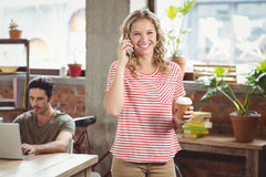 Портрет коммерсантки говоря над телефоном в офисе Стоковые Фото