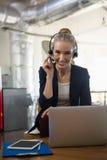 Портрет коммерсантки говоря через шлемофон пока использующ компьтер-книжку в офисе Стоковые Фото