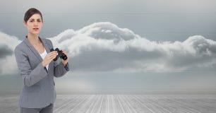 Портрет коммерсантки держа бинокли против неба Стоковое фото RF