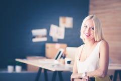 Портрет коммерсантки исполнительного профессионала зрелой сидя на столе офиса Стоковое фото RF