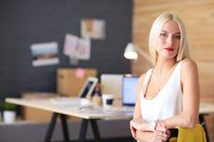 Портрет коммерсантки исполнительного профессионала зрелой сидя на столе офиса Стоковые Изображения