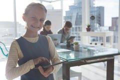Портрет коммерсантки используя таблетку пока коллеги обсуждая в предпосылке Стоковые Фото