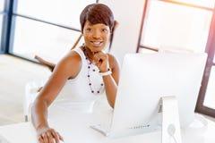 Портрет коммерсантки работая на ее столе в офисе стоковые изображения