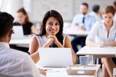 Портрет коммерсантки работая на компьтер-книжке в занятом офисе Стоковое Изображение