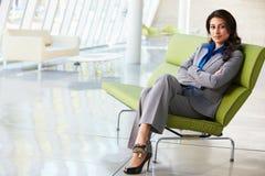 Портрет коммерсантки сидя на софе в самомоднейшем офисе Стоковые Фото