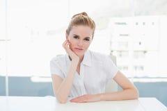 Портрет коммерсантки сидя на столе офиса Стоковые Изображения RF