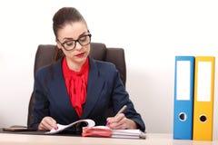 Портрет коммерсантки с компьтер-книжкой пишет на документе на ем Стоковое Изображение