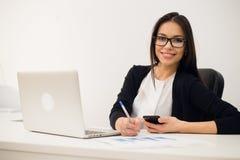 Портрет коммерсантки с компьтер-книжкой пишет на документе на ее офисе Стоковые Изображения