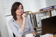 Портрет коммерсантки с компьтер-книжкой пишет на документе Стоковое фото RF