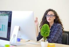 Портрет коммерсантки с компьютером пишет на документе на ее офисе Стоковое Изображение RF