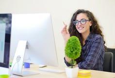 Портрет коммерсантки с компьютером пишет на документе на ее офисе Стоковые Фотографии RF