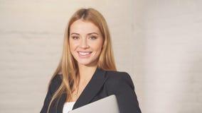 Портрет коммерсантки с ноутбуком, смотря камеру в современном офисе акции видеоматериалы