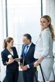 Портрет коммерсантки с чемоданом пока коллеги говоря в предпосылке Стоковые Изображения RF