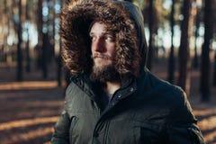 Портрет, конец-вверх молодого стильно серьезного человека с бородой одетой внутри rgreen куртка зимы с клобуком и мехом стоковые изображения