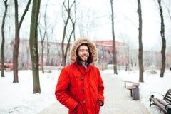 Портрет, конец-вверх человека детенышей стильно одетого усмехаясь с бородой одел в красной куртке зимы с клобуком и мехом на его стоковое фото rf