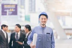 Портрет конструкции, обслуживания и архитектора гражданского инженера строгая в шлеме с предпосылкой города с бизнесменами Стоковое фото RF
