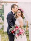Портрет конца-вверх внешний жизнерадостного groom целуя усмехаясь невесту в лбе около свода стоковые изображения rf