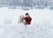 Портрет конца-вверх горизонтальный счастливых пар говоря и смеясь над пока полагающся на стене снега в деревне Стоковая Фотография RF