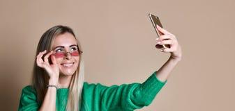 Портрет конца-вверх женщины молодой жизнерадостной моды белокурой в носке свитера делает selfie на смартфоне, над бежевой предпос стоковые изображения