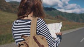 Портрет конца-вверх женщины путешественника турист девушки при рюкзак идя вдоль шоссе задний взгляд сток-видео