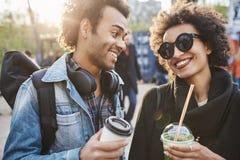 Портрет конца-вверх жизнерадостных молодых пар любовников держа пить и усмехаясь друг к другу пока идущ в парк и Стоковое Изображение
