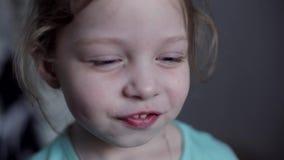 Портрет конца-вверх кавказской жизнерадостной маленькой девочки с голубыми глазами которая ест цыпленка видеоматериал