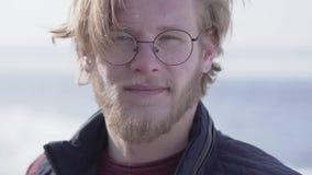 Портрет конца-вверх красивого бородатого человека в стеклах со светлыми волосами смотря в камере усмехаясь outdoors r акции видеоматериалы